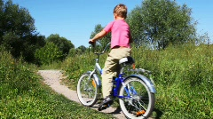 Boy in pink vest and man in turn blue sports suit go on bicycle Stock Footage