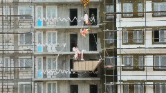 Workers throw out dust from floors of the under construction house Stock Footage