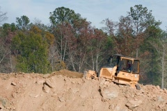 Small Bulldozer moving dirt on a hill Stock Footage
