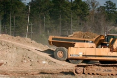 Dump truck and heavy equipment work a construction site Stock Footage