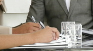Close-up of multi-ethnic business people making notes Stock Footage