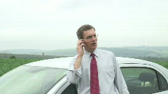 Annoyed businessman talking on cell phone beside his car - stock footage