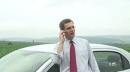 Stock Video Footage of Annoyed businessman talking on cell phone beside his car