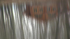 Reflection of a modern log house and autumn trees in the water ripples of a chan Stock Footage