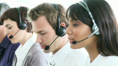 Multi-ethnic business team working in a call-center - stock footage