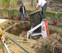 Bobcat digs giant hole for spa Stock Footage