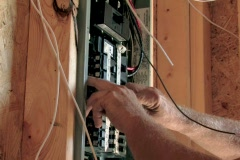 Electrician wiring breaker box in new construction Stock Footage