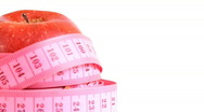 Tape measure wrapped around rotating red apple, loopable Stock Footage
