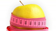 Tape measure wrapped around rotating yellow apple, loopable Stock Footage