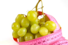 Tape measure wrapped around rotating grapes, loopable Stock Footage