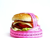 Tape measure wrapped around rotating hamburger Stock Footage