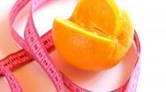 Tape measure wrapped around rotating orange Stock Footage