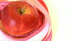 Tape measure wrapped around rotating red apple, loopable - stock footage