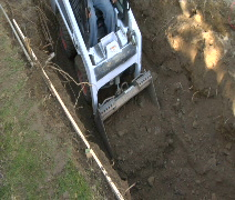 Bobcat digs hole Overhead Stock Footage