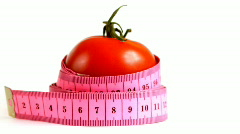 Tape measure wrapped around rotating tomato, loopable Stock Footage