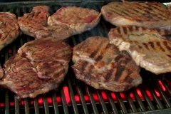 Turning rib eye steak on the grill with audio Stock Footage
