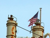 Ragged American flag on top of aging factory Stock Footage