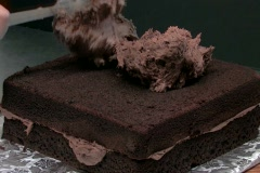 Icing a freshly baked chocolate cake Stock Footage