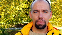 Mans face in yellow jacket close up in park in autumn Stock Footage