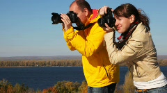 Man and woman takes photocamera in hands and photograph something Stock Footage