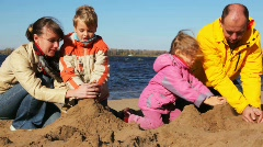 Family of mon, dad, son and daughter build hills of sand together on river Stock Footage