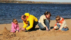 Family of mother, father, son and daughter build hills of sand on river beach Stock Footage