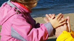 Daughter and father play, clap together in palms on coastline of river Stock Footage