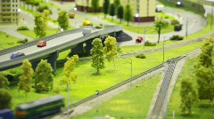 Toy train bring cargo wagon on rail in modern toy city among highway, Stock Footage