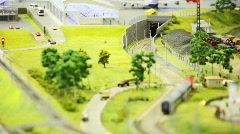 Toy passenger train with two wagon drives to tunnel on rail in toy modern city Stock Footage