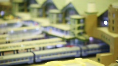 Toy trains stand on platforms in big passenger station with people. Stock Footage
