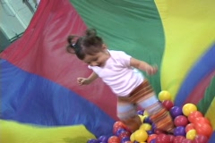 Toddler in jumping gym parachute Stock Footage