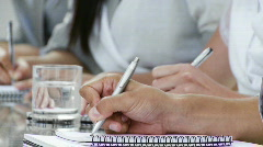Close-up of hands jotting down notes at a conference - stock footage