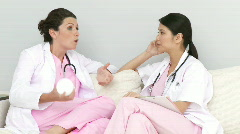 Two talkative nurses relaxing in the staff room Stock Footage