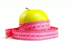 Tape measure wrapped around rotating bitten apple, loopable 1080p - stock footage