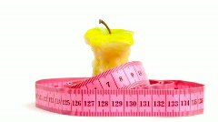 Tape measure wrapped around rotating apple core, loopable 1080p - stock footage
