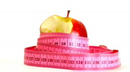 Tape measure wrapped around rotating bitten apple, loopable 1080p Stock Footage