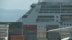 Rear of passing cruise ship behind containers Stock Footage