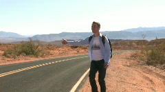 Hitchhiker on a desert road (1 of 2) - stock footage