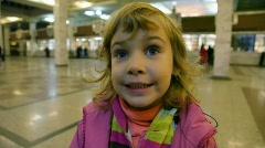 Portrait of little cute caucasian girl standing in ticket office Stock Footage