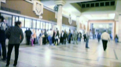 People queueing up in ticket office, camera moving across, blurred Stock Footage