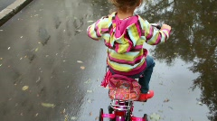 Little girl pedaling on wet asphalt with puddles, camera follow her Stock Footage
