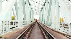 Red-haired young man goes forward on camera on railway bridge Stock Footage
