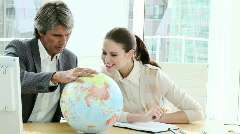 Charismatic business partners looking at a terrestrial globe Stock Footage