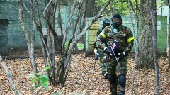 Some players in paintball goes somewhere together on playground Stock Footage