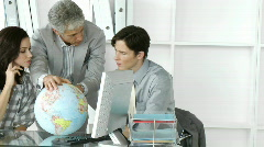 Fortunate business team looking at a terrestrial globe Stock Footage