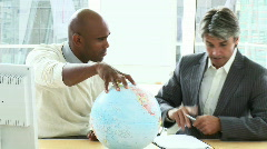 Two ambitious businessmen looking at a terrestrial globe Stock Footage