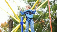 Boy shakes suspended by rubber cords on in park attraction Stock Footage