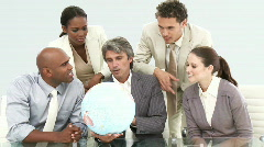 Multi-ethnic business team looking at a terrestrial globe - stock footage