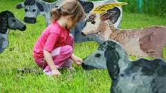 Girl on lawn feeds with grass drawn silhouette of nanny-goat Stock Footage