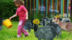 Child goes on lawn and feed from bowls drawn silhouette of nanny-goat Stock Footage